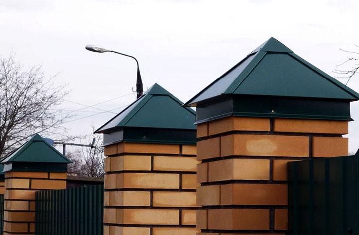 Металлические колпаки на заборе