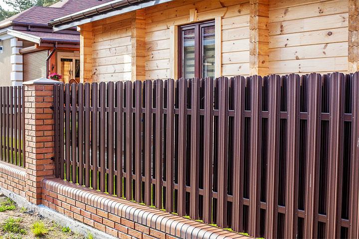 Кирпичный забор с секциями из металлического штакетника