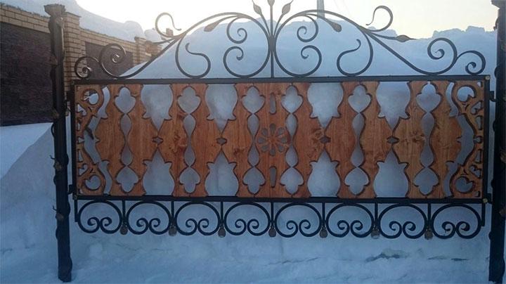 Кованный забор с резными деревянными элементами