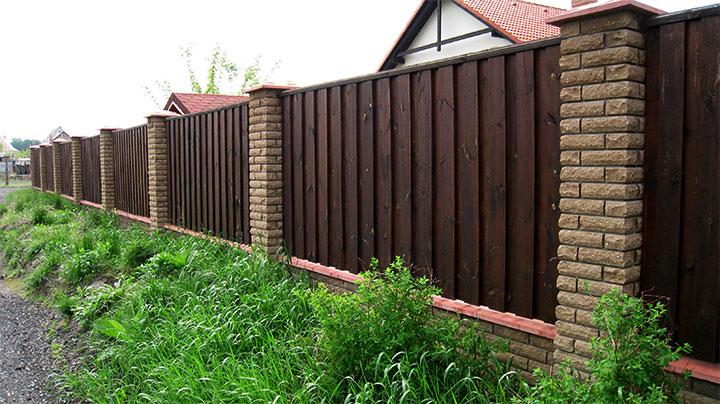 Вертикальный забор из деревянной доски с каменными столбами