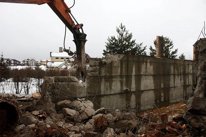 Разрушение бетонного забора спецтехникой