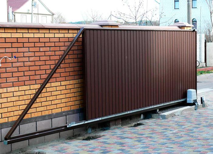 Забор из жёлтого и красного кирпича с раздвижными воротами
