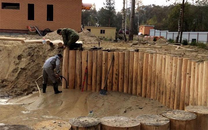 Укрепление стенок котлована бревнами